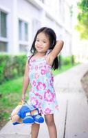 bambina con la bambola in piedi sul sentiero nel parco
