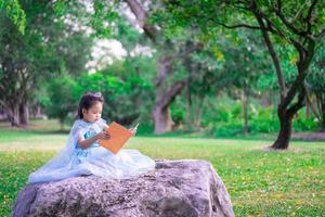 una piccola ragazza asiatica carina che legge un libro