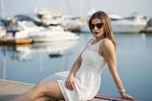 giovane donna seduta vicino al porto turistico