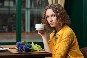 triste giovane donna che beve il tè al ristorante foto