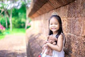 carina bambina asiatica con una bambola nel parco