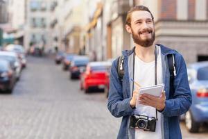 attraente giovane esploratore sta viaggiando attraverso la città