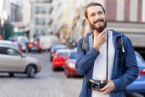 il giovane attraente sta viaggiando e fotografando