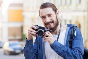 il giovane attraente sta viaggiando e sta facendo le foto