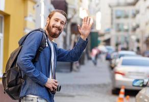 il giovane attraente sta facendo il viaggio attraverso la città