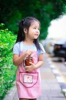 ritratto di bambina in grembiule con mortaio nel parco