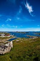 paesaggio estivo norvegese con mare, prato verde e cielo blu profondo