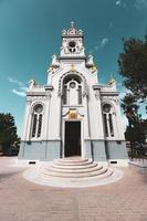 vecchia facciata della chiesa vicino al marciapiede sotto il cielo blu foto