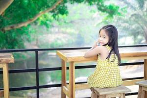 piccola ragazza asiatica che si siede sulla sedia a un tavolo di legno