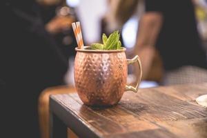 tazza da cocktail in rame sul tavolo di legno