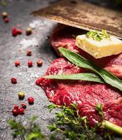bistecca di manzo crudo con erbe, spezie, burro e vecchia mannaia foto