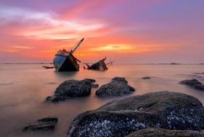 barca da pesca spiaggiata con vista tramonto