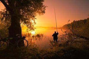 sagoma del pescatore sul lago al tramonto foto