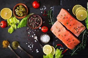 filetto di salmone crudo e ingredienti per cucinare foto