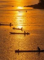 molti pescatori remano in barca a remi per pescare quando il tramonto, silhouet
