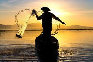 pescatore in azione durante la pesca al mattino foto
