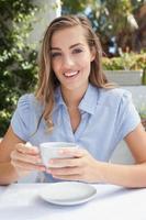 bella donna che mangia un caffè foto