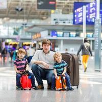 padre e due ragazzini di pari livello all'aeroporto foto