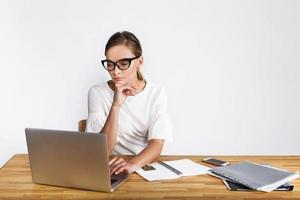 donna premurosa lavora sul computer portatile alla scrivania su sfondo bianco