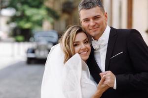 sposa e sposo alla moda sulla vecchia strada europea foto