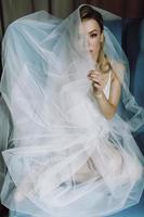 splendida sposa bionda con occhi profondi nascosti sotto un velo blu