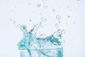 spruzzi d'acqua in un bicchiere su sfondo bianco