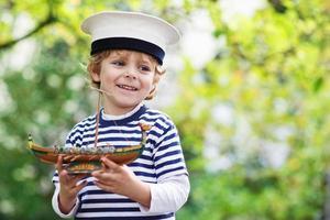 bambino felice in uniforme da skipper che gioca con la nave giocattolo