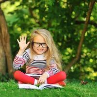 dolce bambina con un libro che mostra cinque - all'aperto