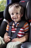 bambino piccolo in un seggiolino per auto con una camicia rossa