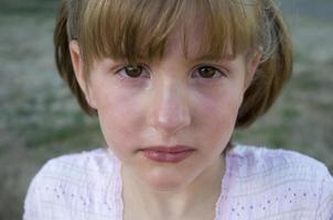 fotografia di una bambina dall'aspetto triste
