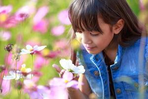 piccola ragazza asiatica in campi di fiori