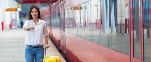 giovane ragazza caucasica con bagagli alla stazione che viaggiano in treno foto