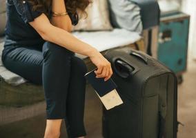 primo piano sulla giovane donna con passaporto, biglietto e bagagli foto