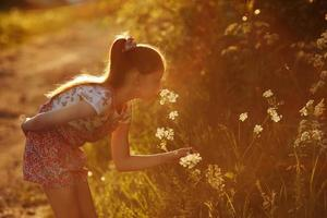 bambina che sente l'odore di un fiore selvatico