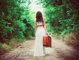 donna con la valigia in mano andando via dalla strada rurale