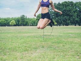 giovane donna che salta nel parco foto