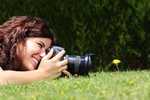 donna che cattura la fotografia di un fiore foto
