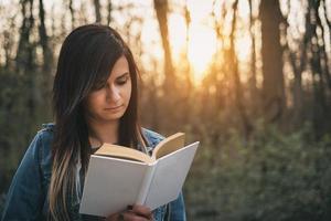 giovane ragazza lettura libro all'aperto