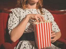 giovane donna che mangia popcorn nel cinema foto