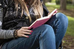 bella ragazza che legge un libro nel parco in autunno
