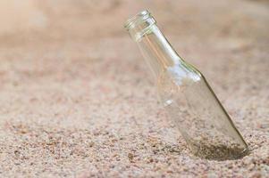bottiglia di vetro vuota nella sabbia