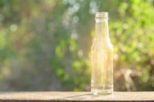 una bottiglia di vetro che brilla su un pavimento di legno