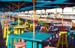 tavoli colorati e sgabelli con ombrelloni