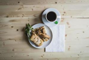 colazione con pasticcini da tè e fiori bianchi sulla tavola di legno foto