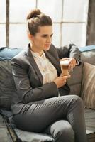 donna d'affari con caffè latte seduto sul divano in appartamento