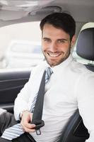 uomo d'affari che mette sulla sua cintura di sicurezza foto