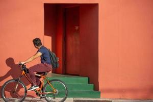 miami, florida, 2020 - uomo che guida la bicicletta davanti a un edificio colorato