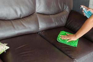 persona che pulisce il divano in pelle