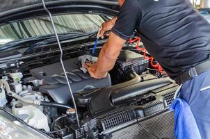 persona che dettaglia il motore dell'auto