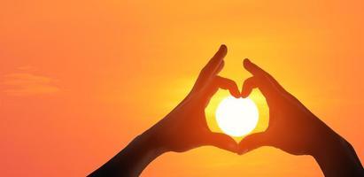 mani che fanno un simbolo a forma di cuore foto